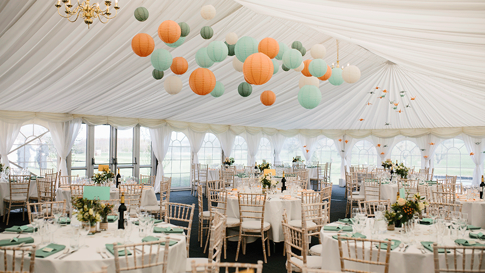 Complementary coloured paper lanterns warm up a white for Indoor marquee decoration