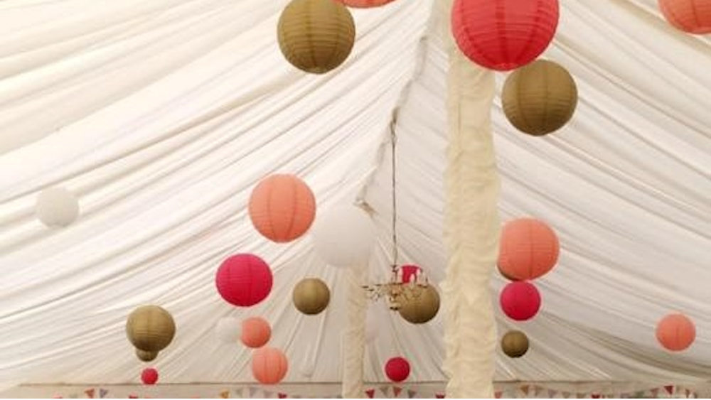 Coral and Gold Lanterns Brighten a Traditional Pole Tent