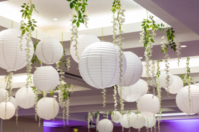 White wedding lanterns interspersed with wisteria