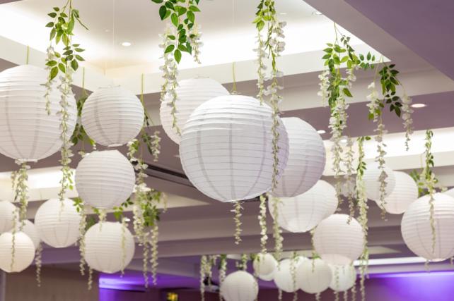 White wedding lanterns interspersed with wisteria